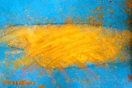 underlying: Peeling blue orange paint on a metal surface exposing underlying rusty metal Stock Photo