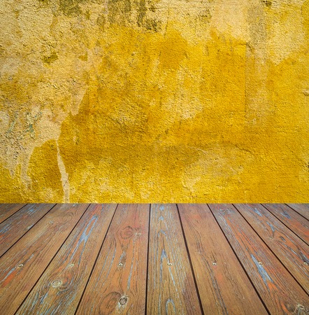 damaged cement: Room interior: yellow damaged cement wall with brown wooden floor Stock Photo