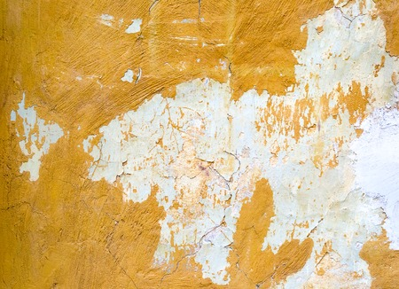 Cracked painted yellow concrete wall background or texture