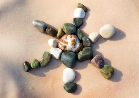 white pebble: Female body skin, sun symbol made of white pebble stones