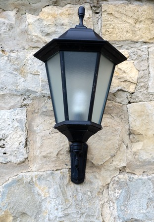 lamp post: Close-up view of vintage lantern on stone wall Stock Photo