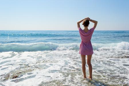 cuerpo femenino: Mujer joven morena en vestido de verano de pie por el mar azul y mirando al horizonte. Cauc�sica hermosa chica de relax y disfrutar de la paz de vacaciones.