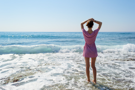 hot day: Young brunette woman in summer dress standing by blue sea and looking to horizon. Beautiful caucasian girl relaxing and enjoying peace on vacation.