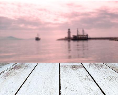 vague: Phare et voile navires dans la mer au coucher du soleil, Alanya, Turquie, planche en bois en perspective Banque d'images