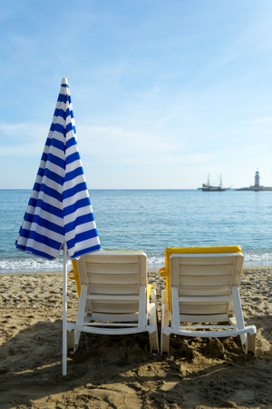 blue romance: Two chairs and closed umbrella on  the beach with sea view