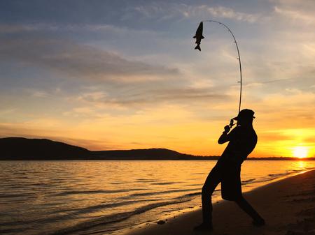 Joven pesca al atardecer Foto de archivo - 89460200
