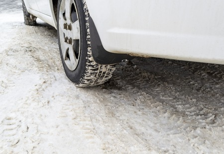 Car tyres on winter road covered with snow