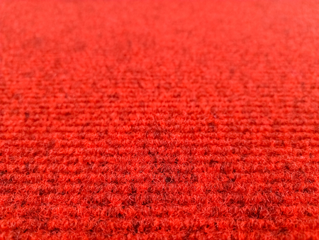 Red woolen carpet background with perspective view, selective focus