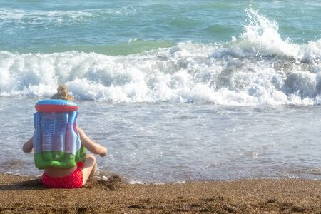 Little girl sitting back in a life jacket at the beach and looking at sea waves Zdjęcie Seryjne