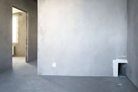 Unfinished building. Rough finish of the apartment. A large empty room with plastered concrete walls. Interior renovation.