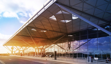 Stansted Airport building, London UK - March 2014, in the sun light and sky reflection