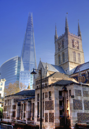 LONDON, UK - MARCH 29, 2014  Southwark Cathedral and Shadr of glass  South bank walk of the river Thames  Contrast modern and old architecture  HDR proceeding image