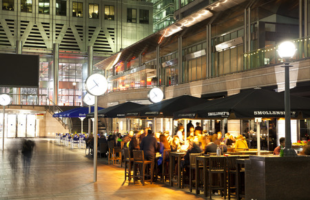 chilling out: LONDON, CANARY WHARF UK - APRIL 4, 2014   Canary Wharf square view in night lights with office workers chilling out after working day in local cafes and pubs