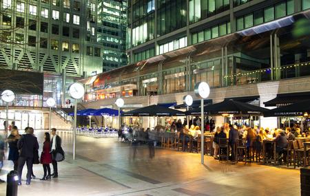 chilling out: LONDRES, Canary Wharf Reino Unido - 04 de abril 2014 Canary Wharf vista cuadrado en luces de la noche con los oficinistas relajarse despu�s de d�as de trabajo en los caf�s y pubs de la zona