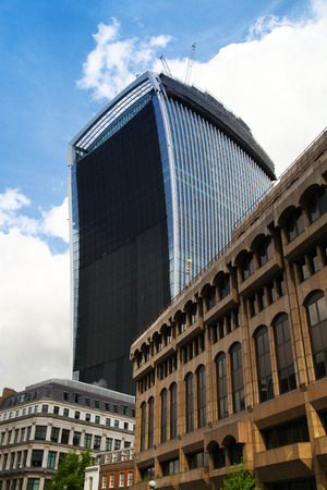 LONDON, UK - APRIL 24, 2014  Famous Walkie Talkie building still keeps iconic glass wall cowered  Wall was covered after it had started reflect very strong sun hit down on properties, roads and cars Stock Photo - 28196077