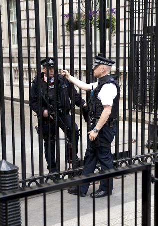LONDON, UK - MAY 14, 2014  - Policemen on duty, Security officers in front of PM s residence at Downing Street 10  Parliament street in London, the address for ministries and government institutes