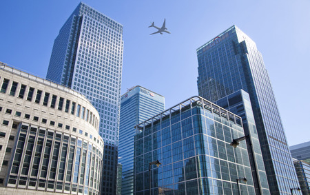 LONDON, UK - JULY 20, 2014  Aircraft over the London s skyscrapers going to land in the City airport