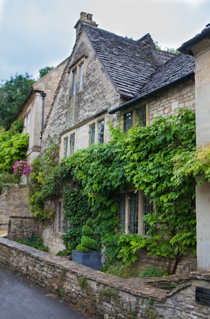 english village: WILTSHIRE, CHIPPENHAM, UK - AUGUST 9, 2014: Castle Combe, unique old English village and luxury golf club