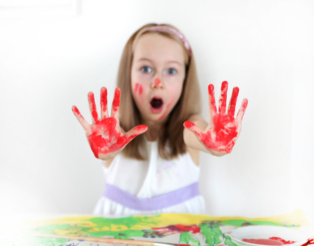 little girl surprised: Girl drawing with water colours