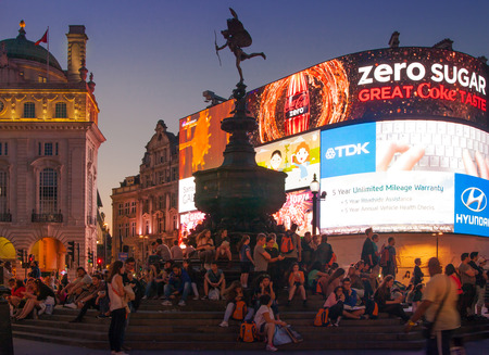 LONDON, UK - AUGUST 22, 2014: Piccadilly Circus in night. Famous place for romantic dates. Square was built in 1819 to join of Regent Street