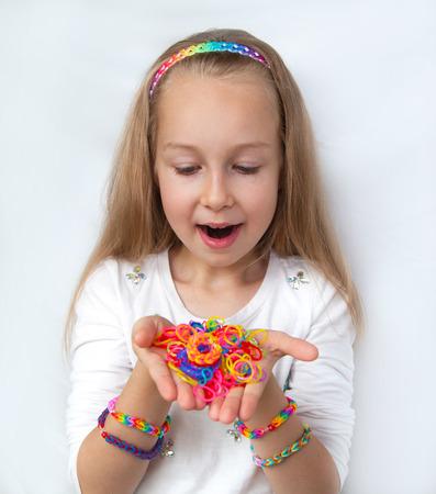 rubber bands: Loom bags craft. Little girl demonstrating her works.