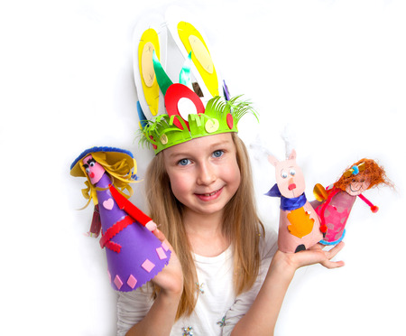 Little girl demonstrating her craft works and Easter bonnet photo