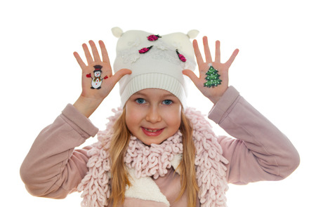 Happy girl demonstrating Christmas symbols painted on her hands. Snowman and Christmas tree photo
