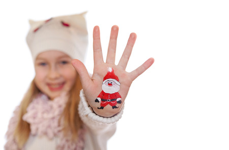 Happy girl demonstrating painted Christmas symbols on her hands. Santa Claus, Christmas tree, Snow man and etc photo