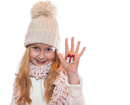 Happy girl demonstrating painted Christmas symbols on her hands. Present box photo