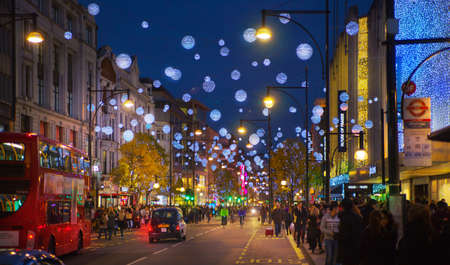london landmark: LONDON, UK - NOVEMBER 30, 2014: Christmas lights on Oxford street with crowd of people making christmas shopping