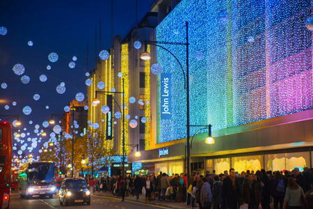 bargain hunting: LONDON, UK - NOVEMBER 30, 2014: Christmas lights on Oxford street with crowd of people making christmas shopping