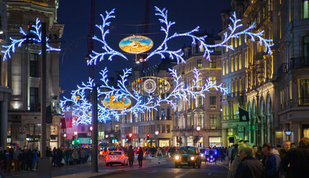 LONDON, UK - NOVEMBER 30, 2014: Christmas lights on Regent street with crowd of people making christmas shopping
