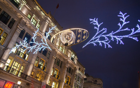 bargain hunting: LONDON, UK - NOVEMBER 30, 2014: Christmas lights on Regent street with crowd of people making christmas shopping