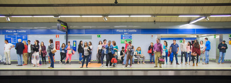 commuters: MADRID, SPAIN - MAY 28, 2014: Tube, underground station with commuters awaiting train