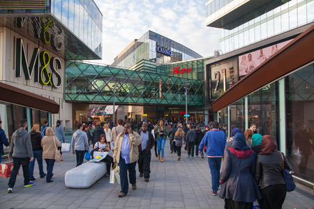 bargain hunting: LONDON, UK - NOVEMBER 29, 2014: Stratford village square and big shopping centre decorated with Christmas lights and lots of people shopping around