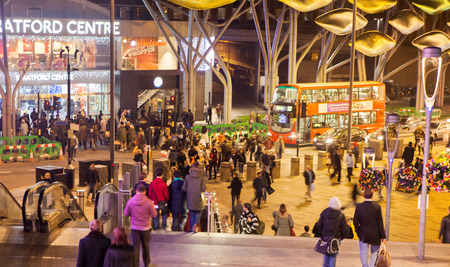 bargain hunting: LONDON, UK - NOVEMBER 29, 2014: Stratford village square with shopping centre entrance and central bus stop and lots of people in Christmas rush