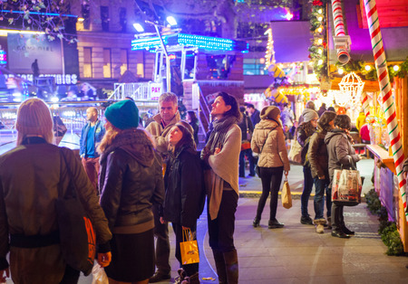 fun fair: LONDON, UK - NOVEMBER 30, 2014 - Leicester square traditional fun fair with stools, carrousel, prises to win and Christmas activity. People and families enjoying Christmas mood night out
