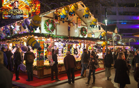 carrousel: London, Leicester square traditional fun fair with stools, carrousel, prises to win and Christmas activity. People and families enjoying Christmas mood night out
