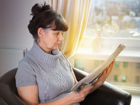 experiencing: Pension age good looking woman reading news