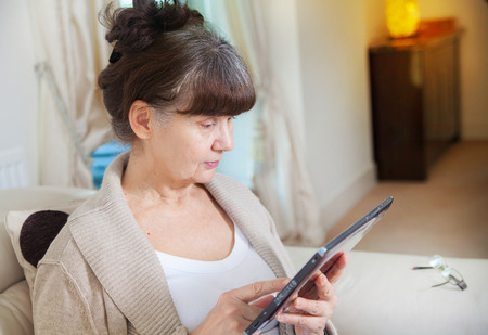 woman searching: Pension age good looking woman searching in internet on tablet device