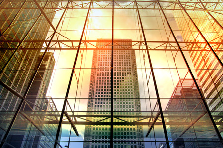 LONDON, UK - MAY 14, 2014: Office buildings of Canary Wharf. Modern architecture the leading centre of global finance in sun set lights