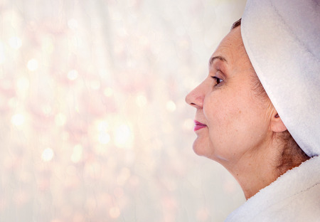 towel head: Spa concept portrait. Aged good looking woman with white towel on her head Stock Photo