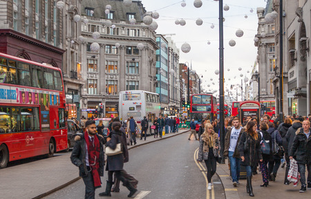 regent: LONDON, UK - NOVEMBER 30, 2014: Regent street, Oxford circus with lots of pedestrians and cars, taxis on the road.