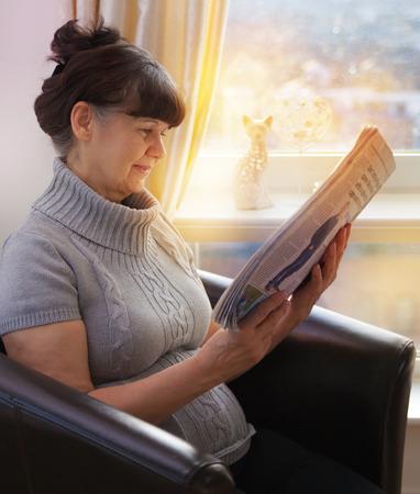 good looking woman: Pension age good looking woman reading newspaper