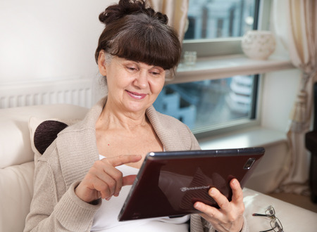good looking woman: Pension age good looking woman searching on tablet