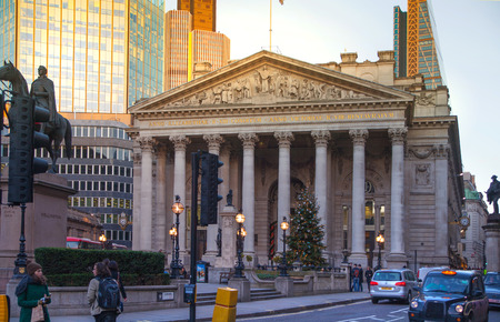 route master: LONDON, UK - DECEMBER 19, 2014: Royal Exchange building in sun set and square with lots of office people passing the Bank street.