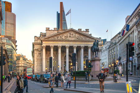 LONDON, UK - DECEMBER 19, 2014: Royal Exchange building in sun set and square with lots of office people passing the Bank street.