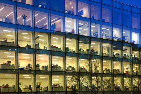 LONDON, UK - DECEMBER 19, 2014: Office block with lots of lit up windows and late office workers inside. City of London business aria in dusk.