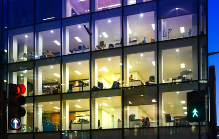 LONDON, UK - DECEMBER 19, 2014: Office block with lots of lit up windows and late office workers inside. City of London business aria in dusk. Imagens - 38219375