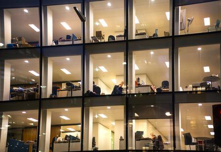LONDON, Verenigd Koninkrijk - 19 december 2014: Kantoorgebouw met veel verlichte ramen en laat kantoormedewerkers binnen. City of London zakelijke aria in de schemering.